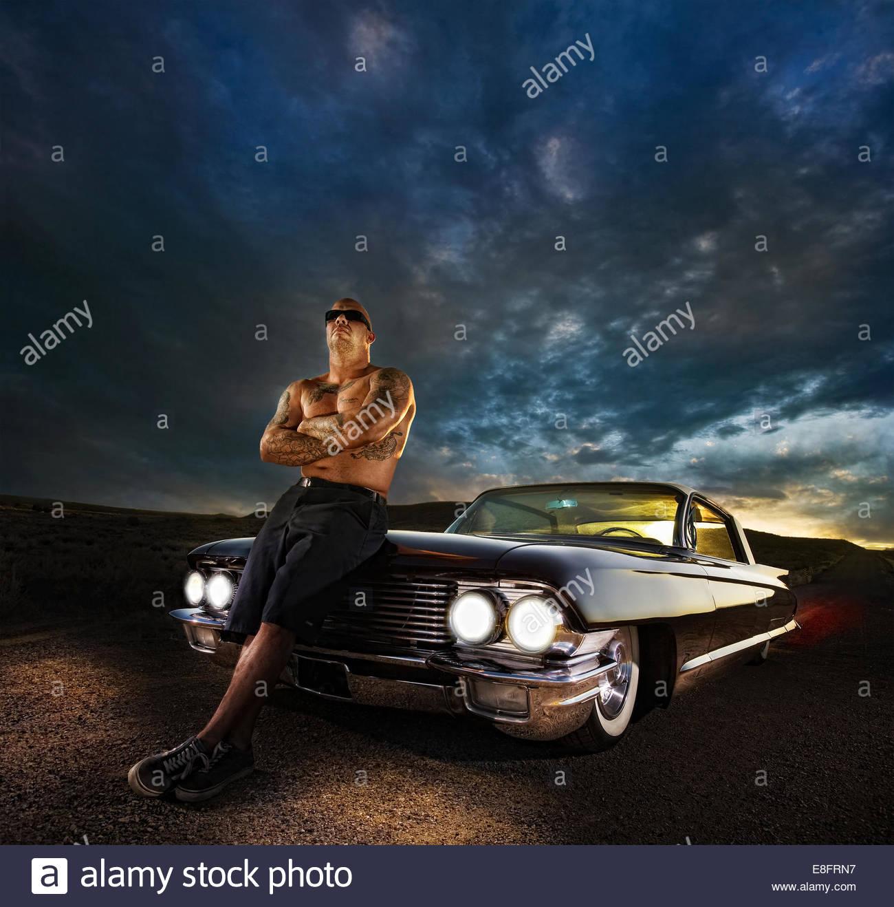 Tattooed man appuyé contre sa voiture d'époque Photo Stock