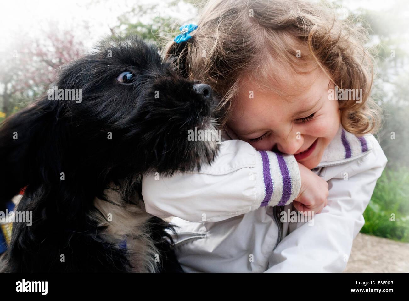 L'Italie, petite fille (4-5) en jouant avec chiot Photo Stock