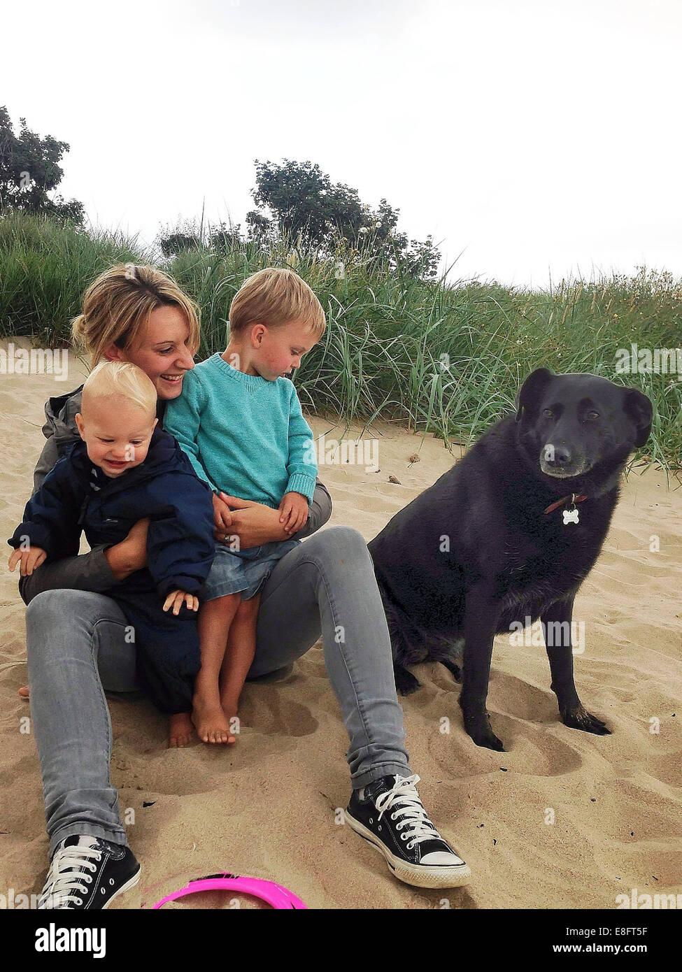 Portrait d'une mère assis sur la plage avec deux fils et le chien Photo Stock