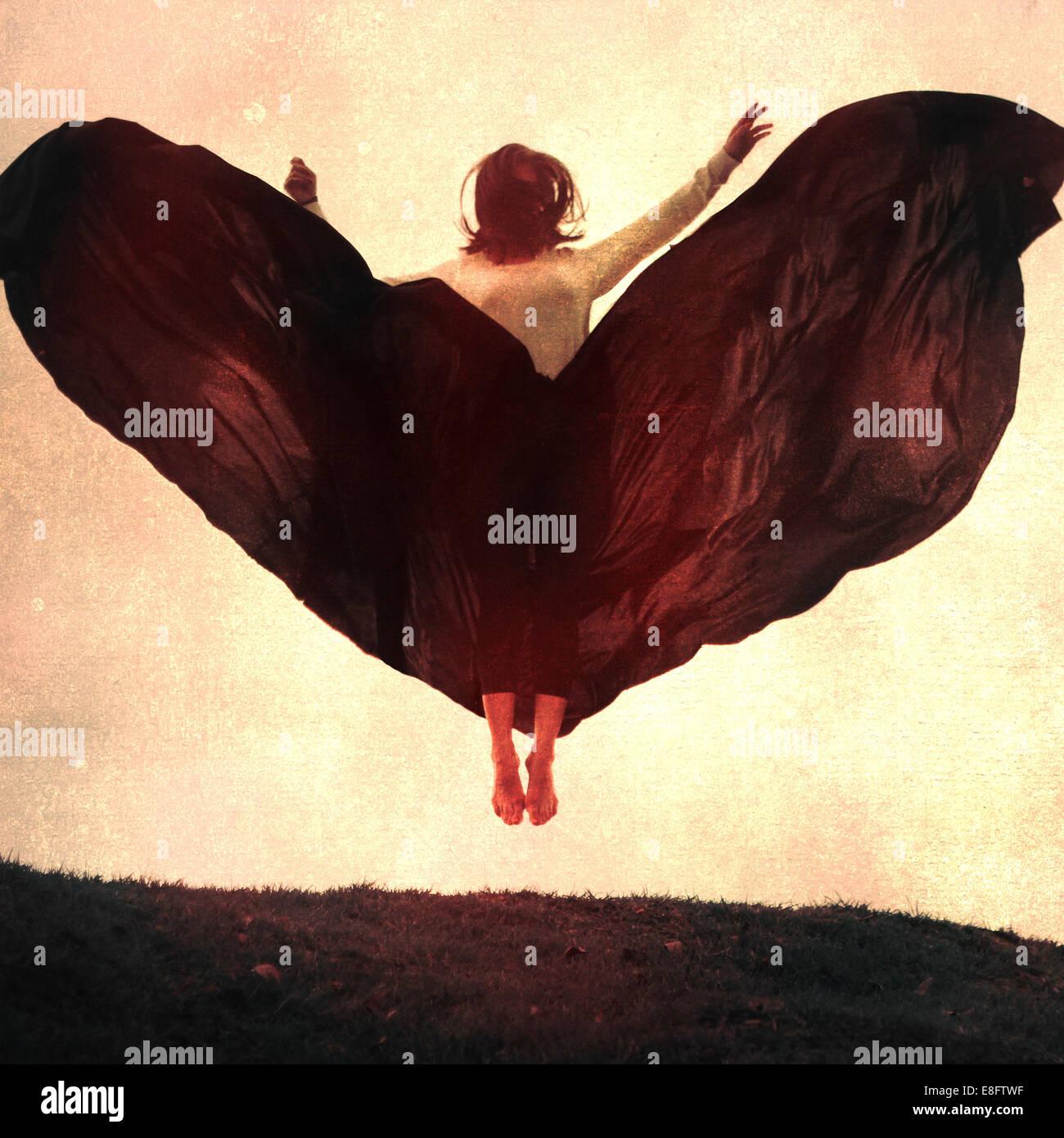 Femme portant jupe fluide en sautant dans l'air Photo Stock