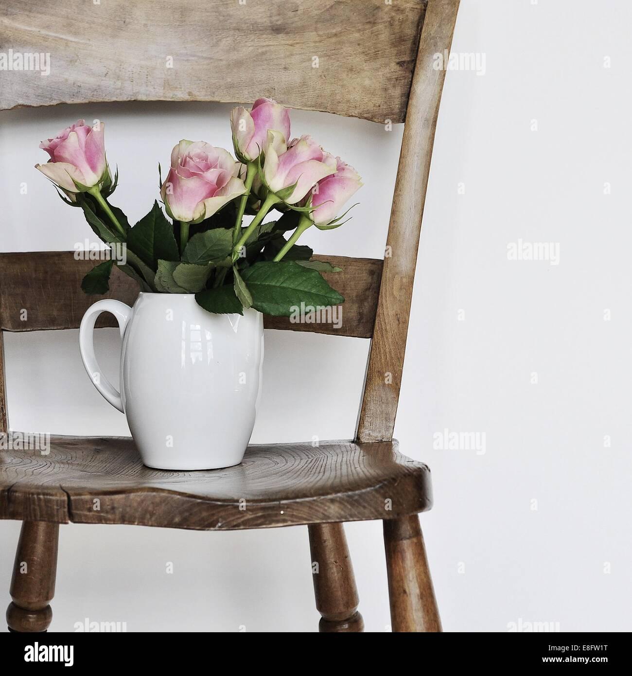 Vase de fleurs sur la chaise en bois Photo Stock
