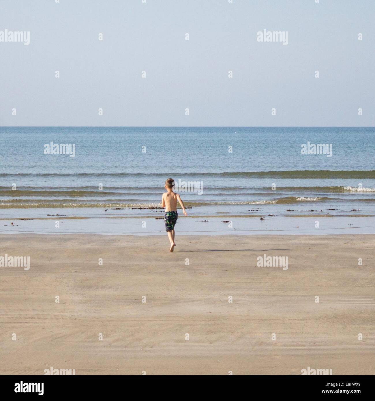 Boy (6-7) s'exécutant dans la mer Photo Stock