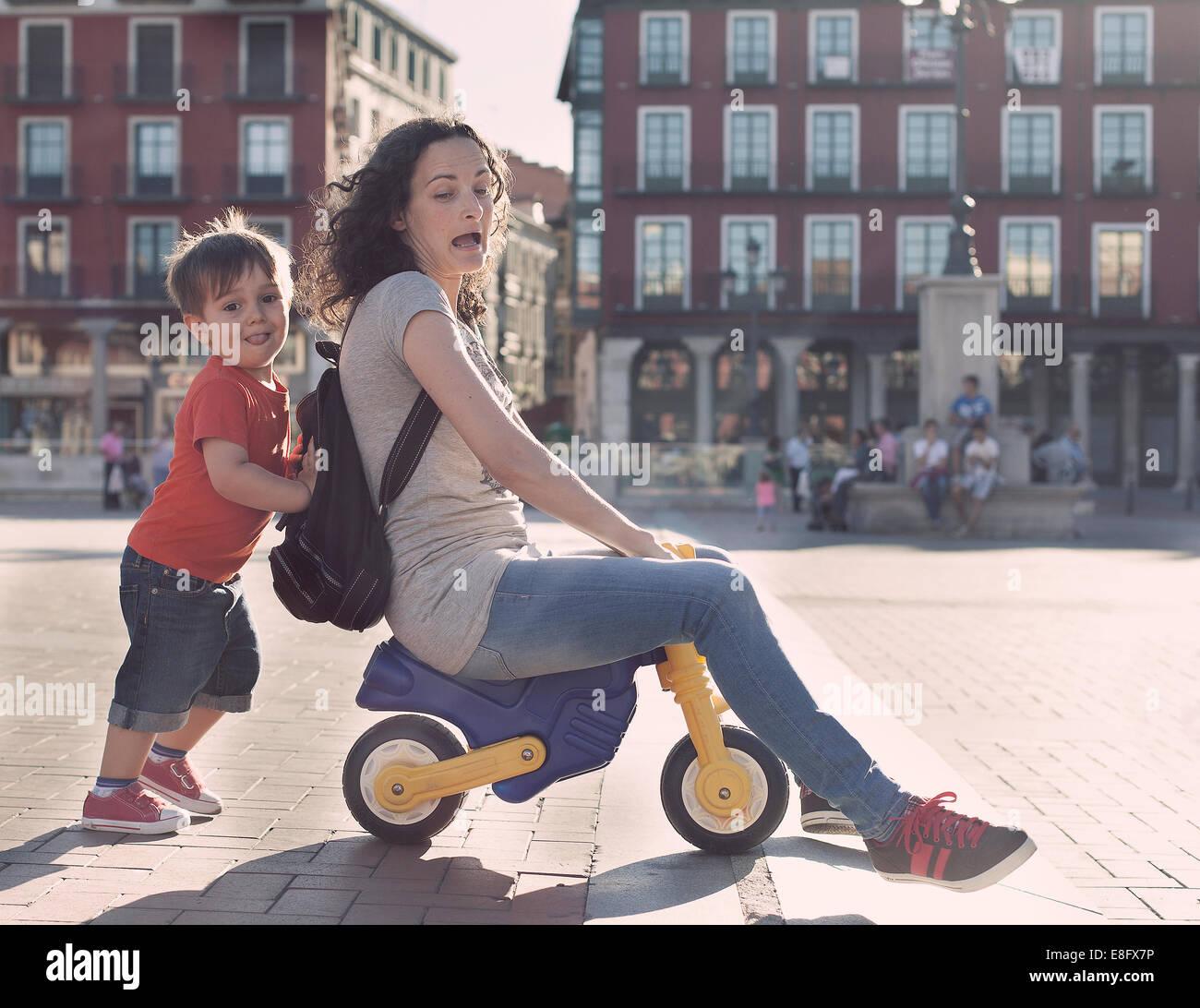 Garçon poussant sa mère sur un tricycle jouet Photo Stock