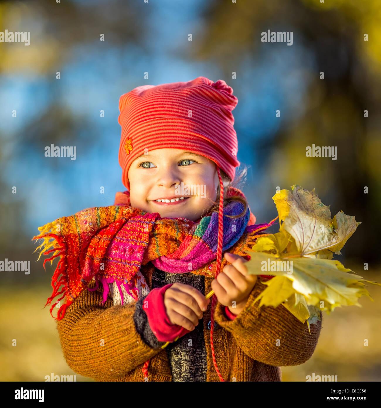 Petite fille jouant avec les feuilles d'automne Photo Stock