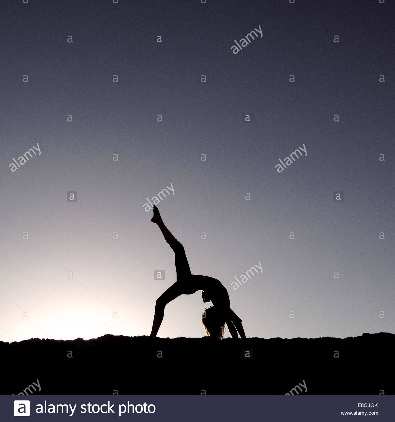 Woman doing yoga at beach à l'aube Photo Stock