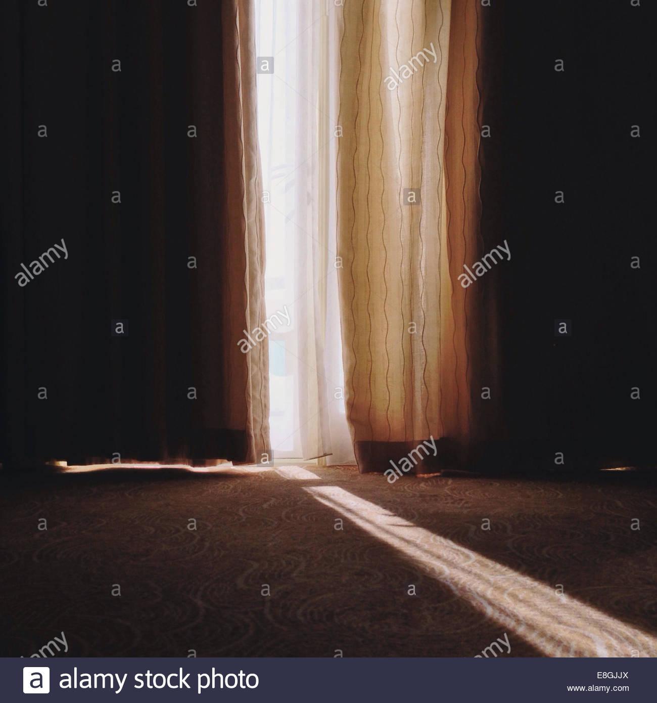 Sunbeam qui brillait à travers les rideaux en écart Photo Stock