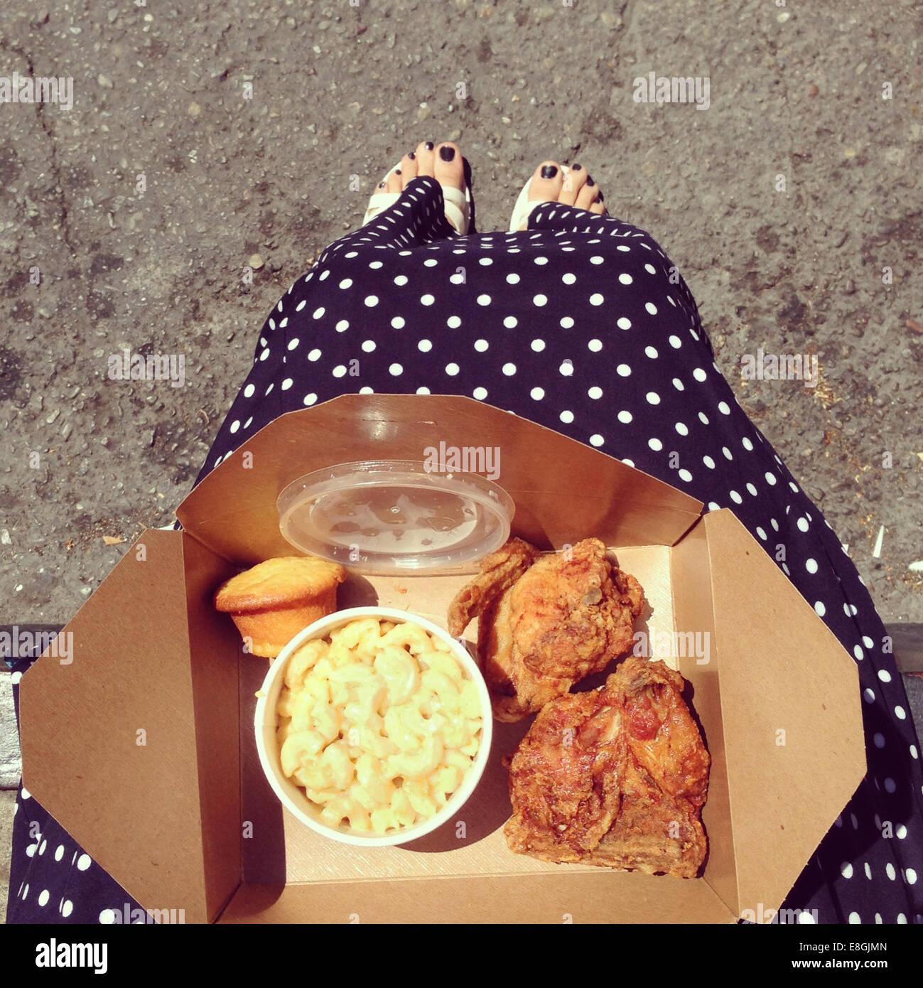 Femme avec un poulet frit à emporter Photo Stock