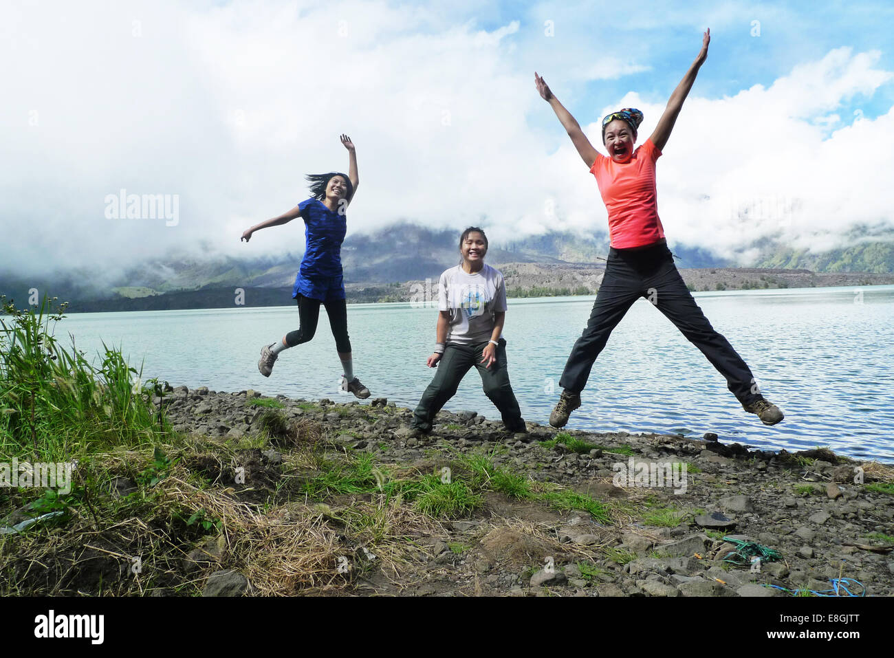 L'Indonésie, Nusa Tenggara Ouest, Mataram, Mont Rinjani, cheerful women jumping by lake Banque D'Images