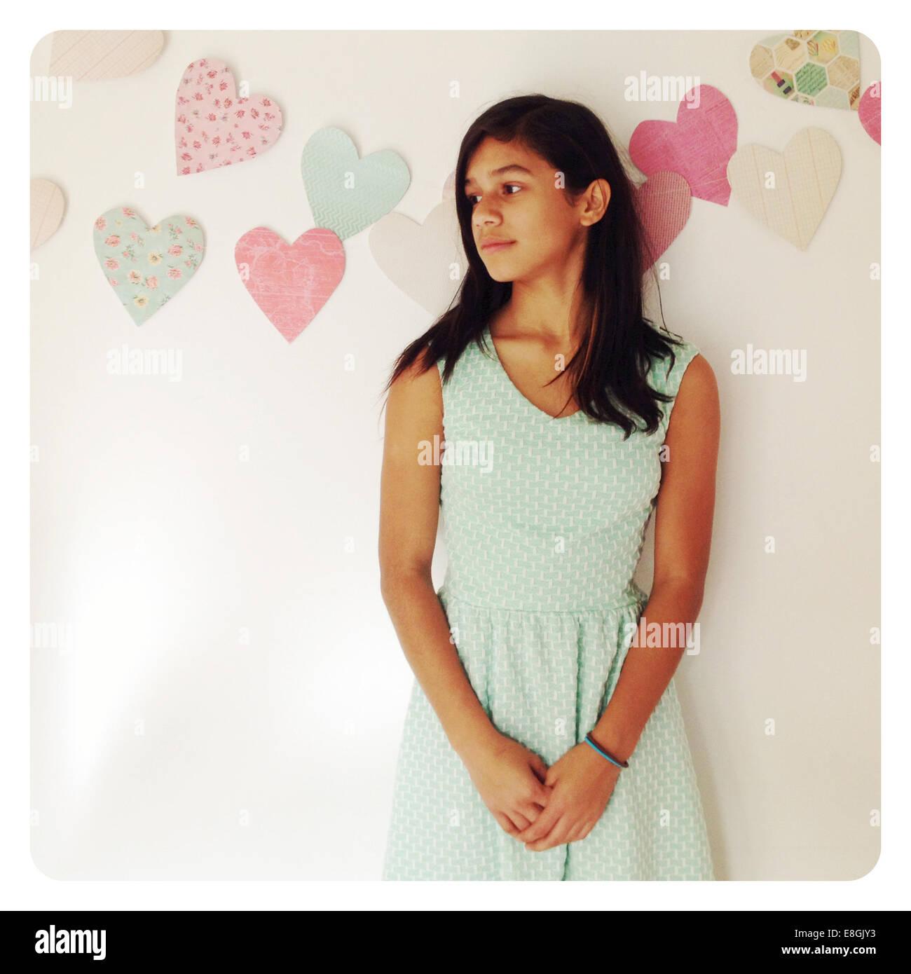 Girl appuyé contre un mur à côté Photo Stock