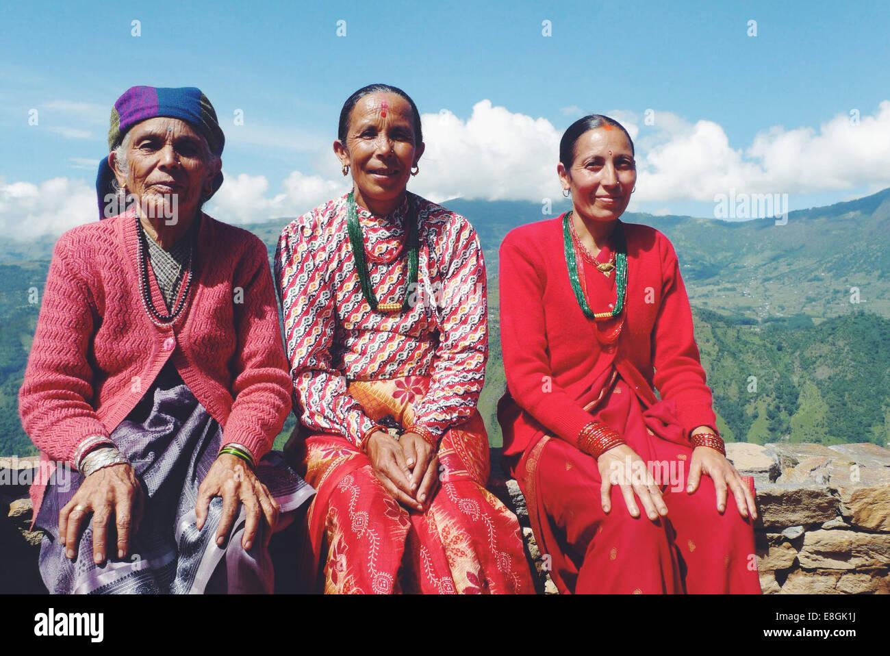 Le Népal, Portrait de femme assise sur mur de pierre en montagne Photo Stock