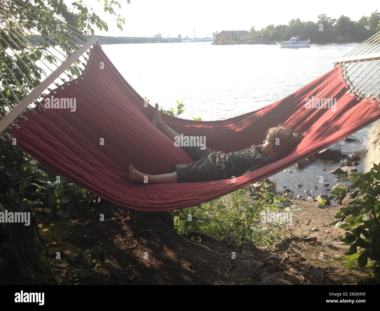 Petit garçon se reposant dans un hamac sur un beau jour d'été par l'eau Photo Stock