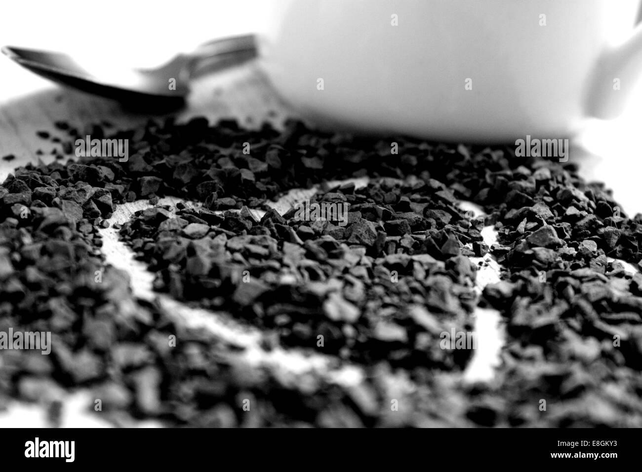 Un coeur dessiné dans les granules de café le long d'une petite cuillère en argent et blanc mug Photo Stock