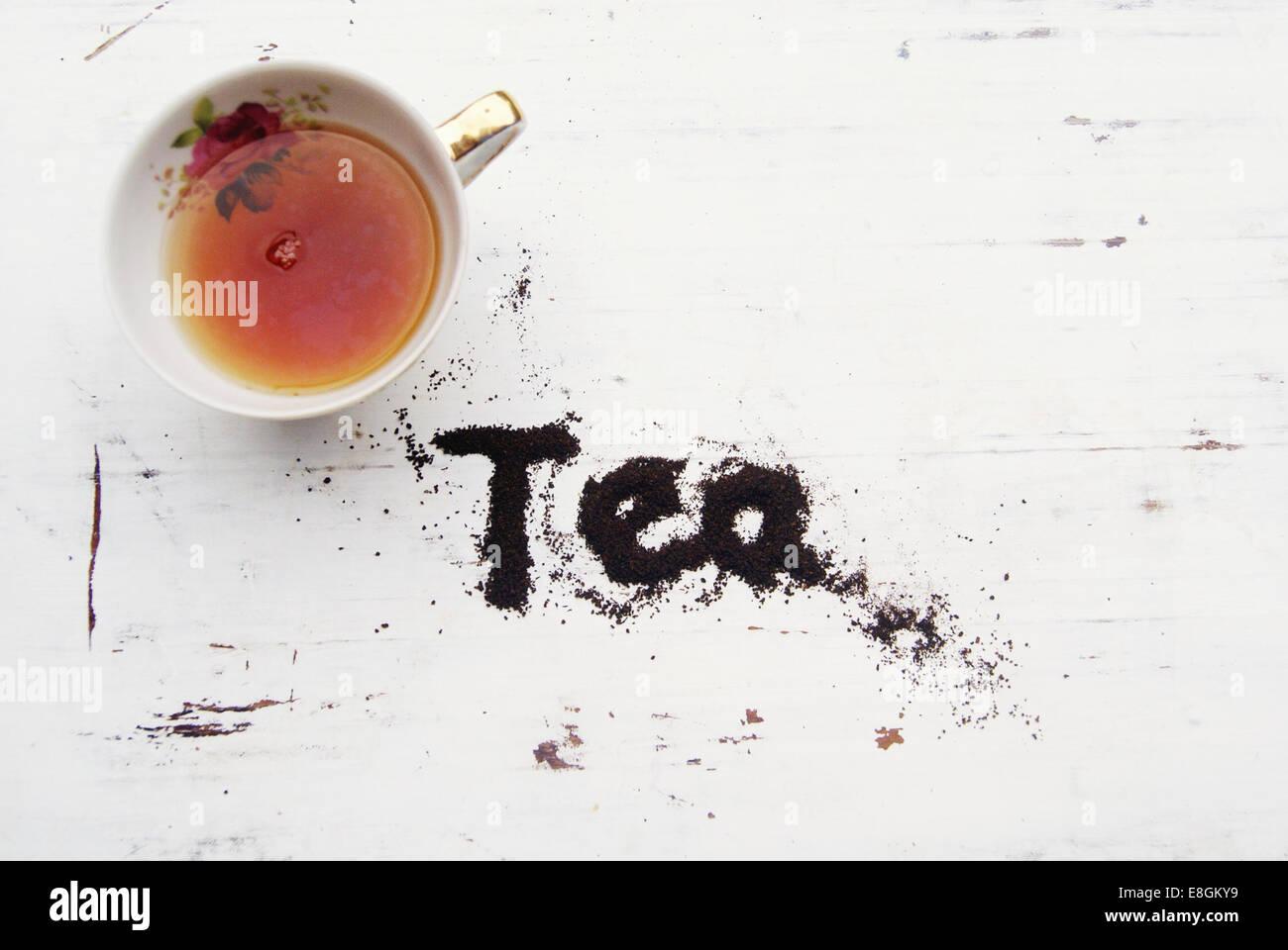 Tasse de thé avec thé mot épelé dans les feuilles de thé Photo Stock