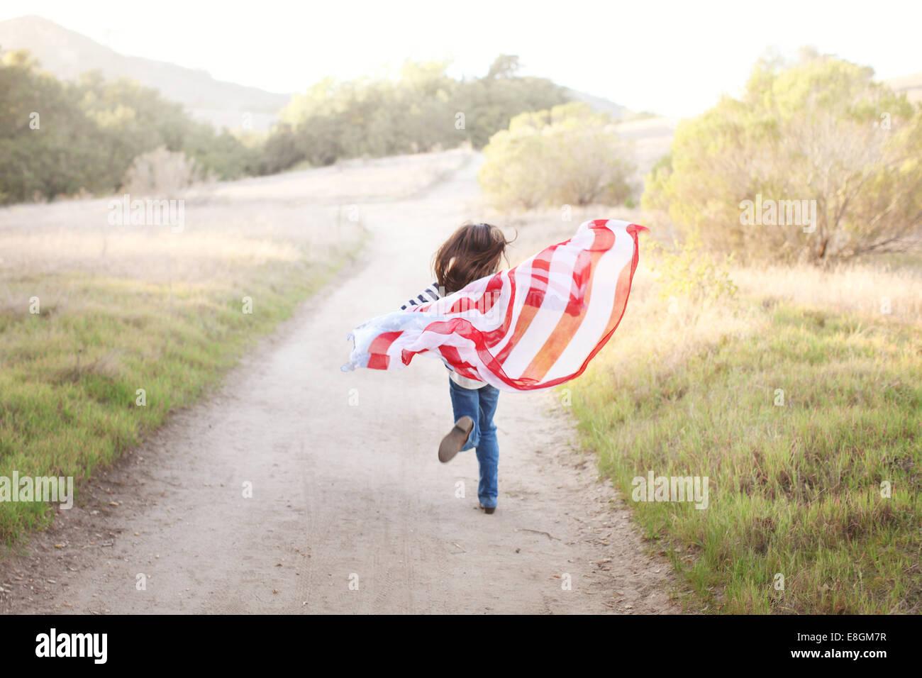 Vue arrière de Girl courir le long d'un sentier tenant un drapeau américain, USA Banque D'Images