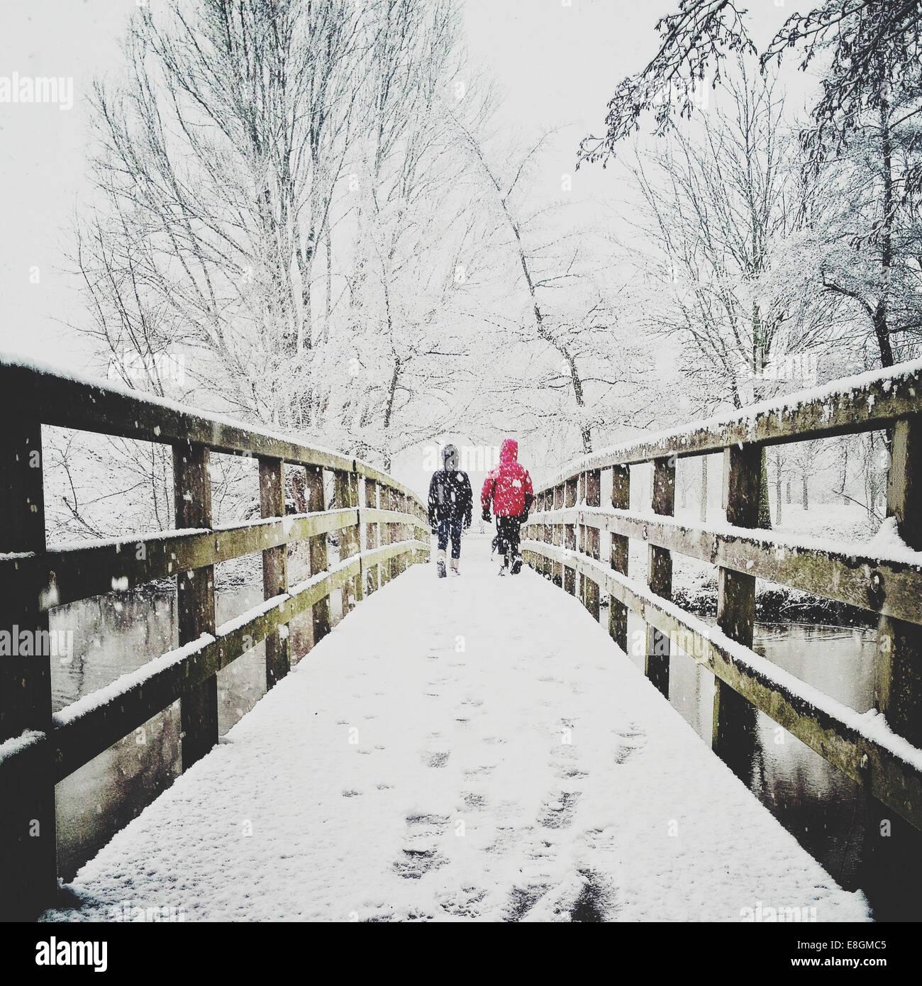 Vue arrière de deux enfants qui traversent la passerelle dans la neige Banque D'Images