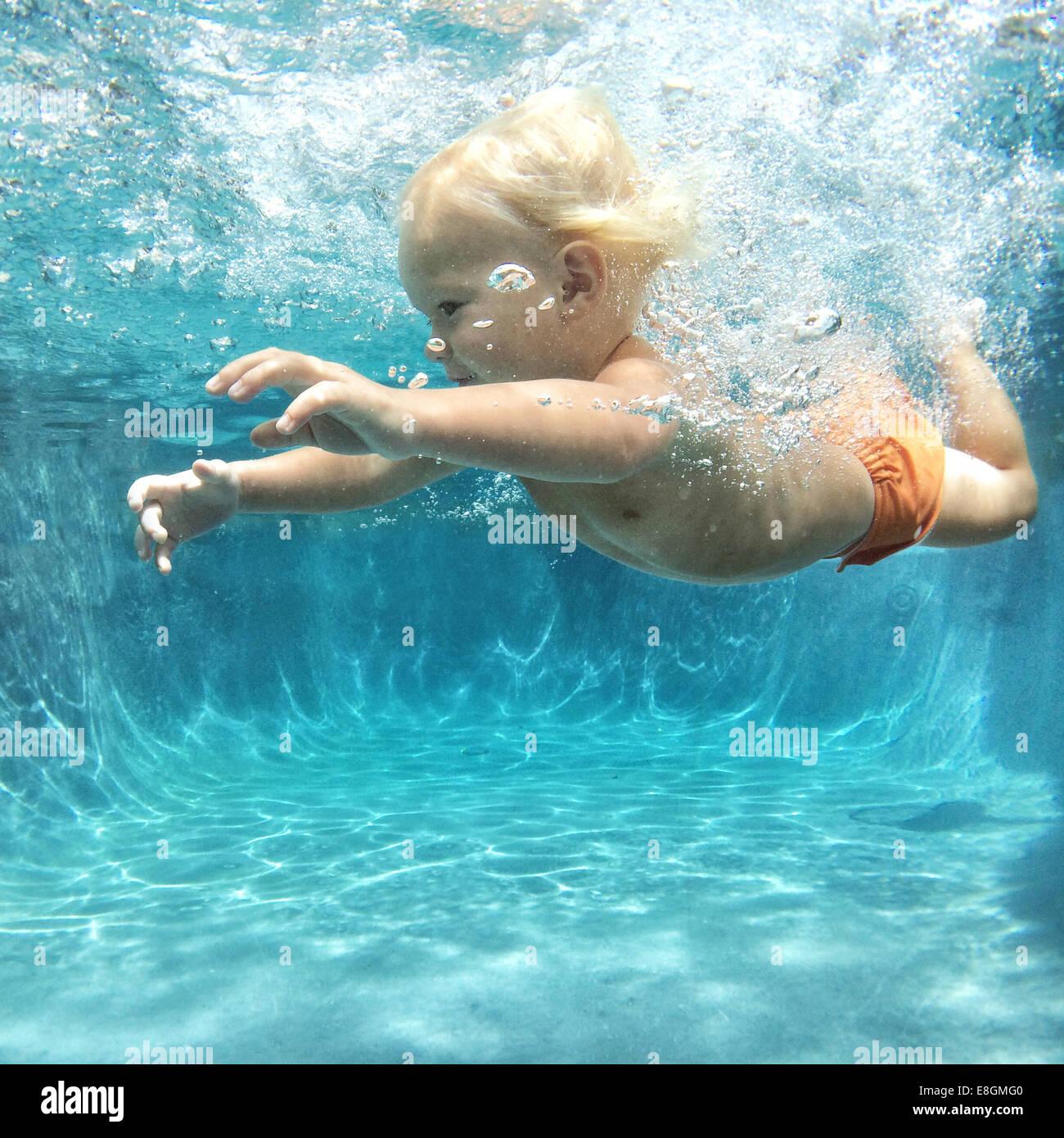 Boy swimming underwater Photo Stock