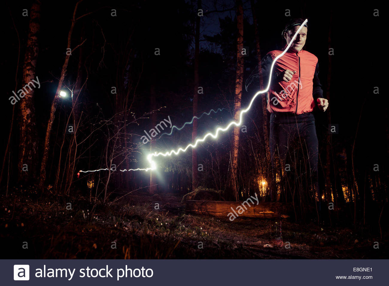 Homme qui court avec light trails in forest Photo Stock