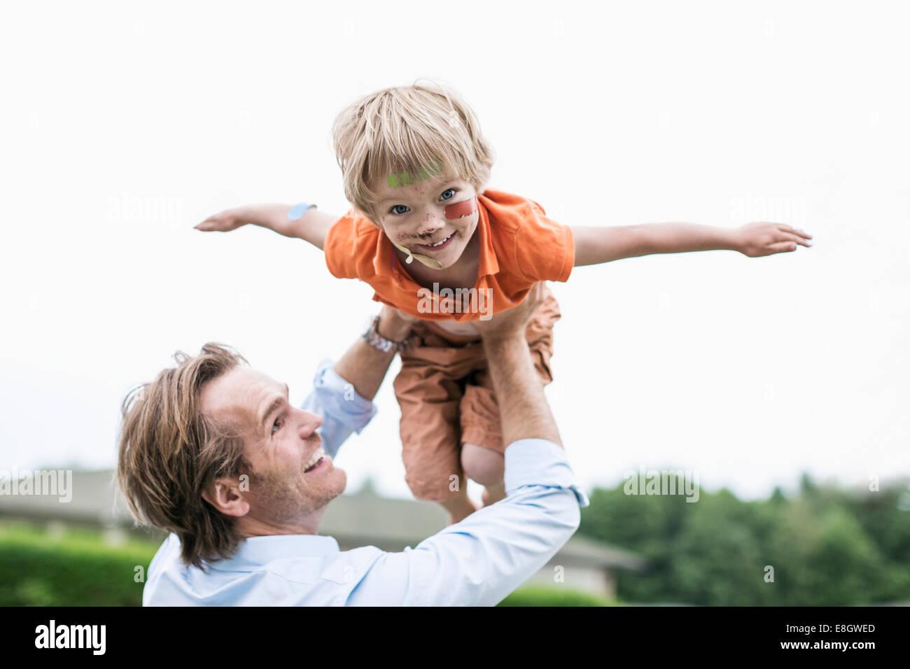 Père fils blessés ludique de levage contre ciel clair Photo Stock