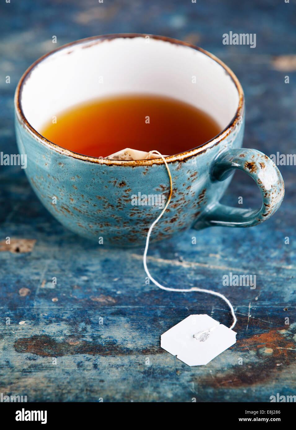 Tasse de thé avec sachet on blue background Photo Stock