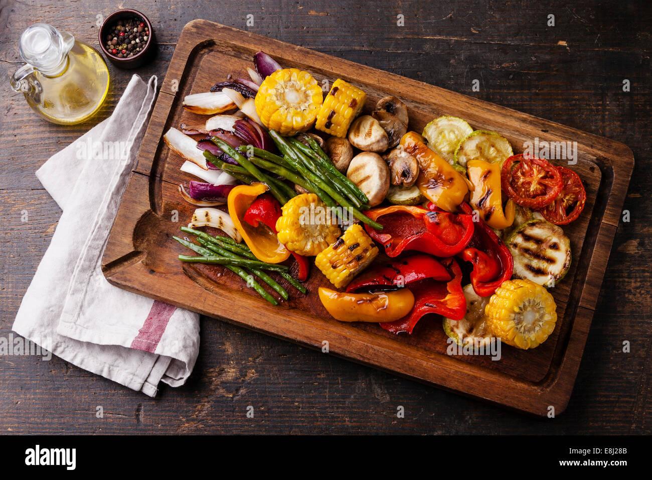 Légumes grillés sur une planche à découper sur fond de bois foncé Photo Stock