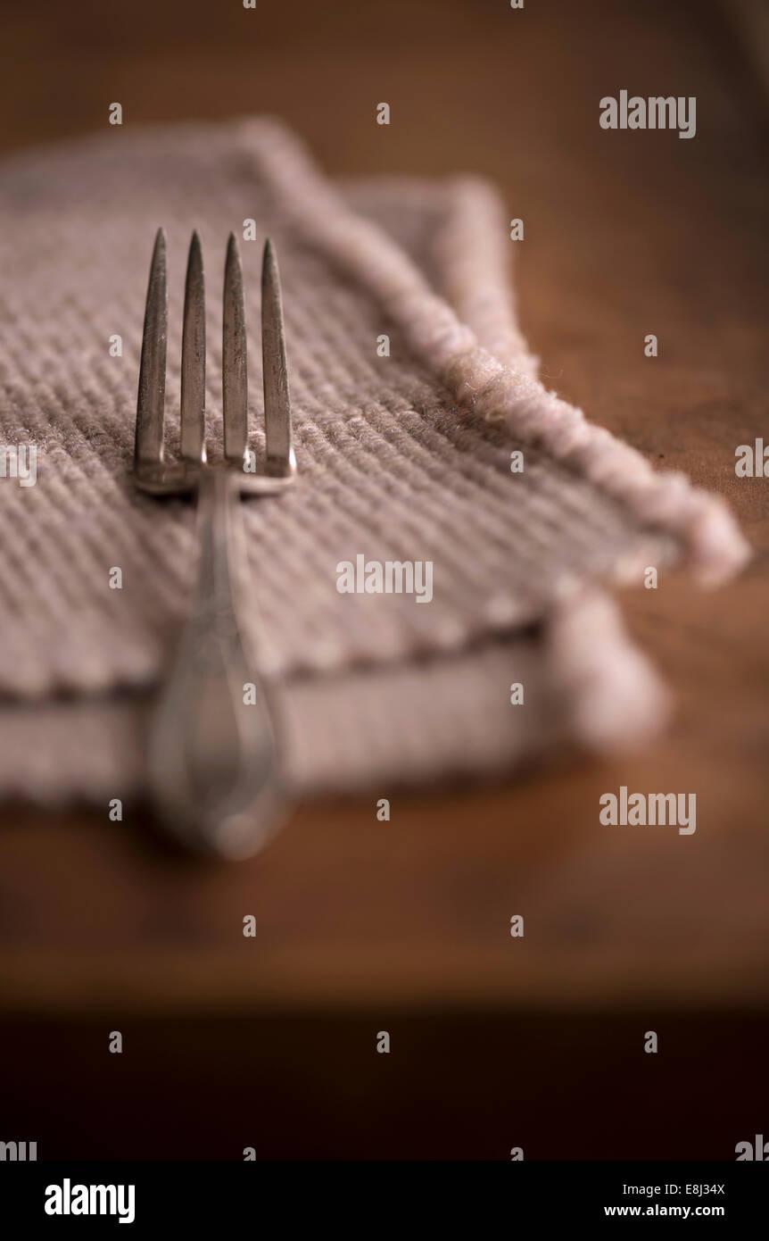 Réglage simple avec un mobilier ancien et d'un napperon vintage de fourche sur une table rustique en bois Photo Stock
