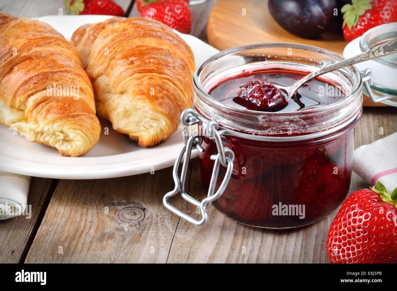 La confiture de fraise et un croissant sur la table en bois. Photo Stock