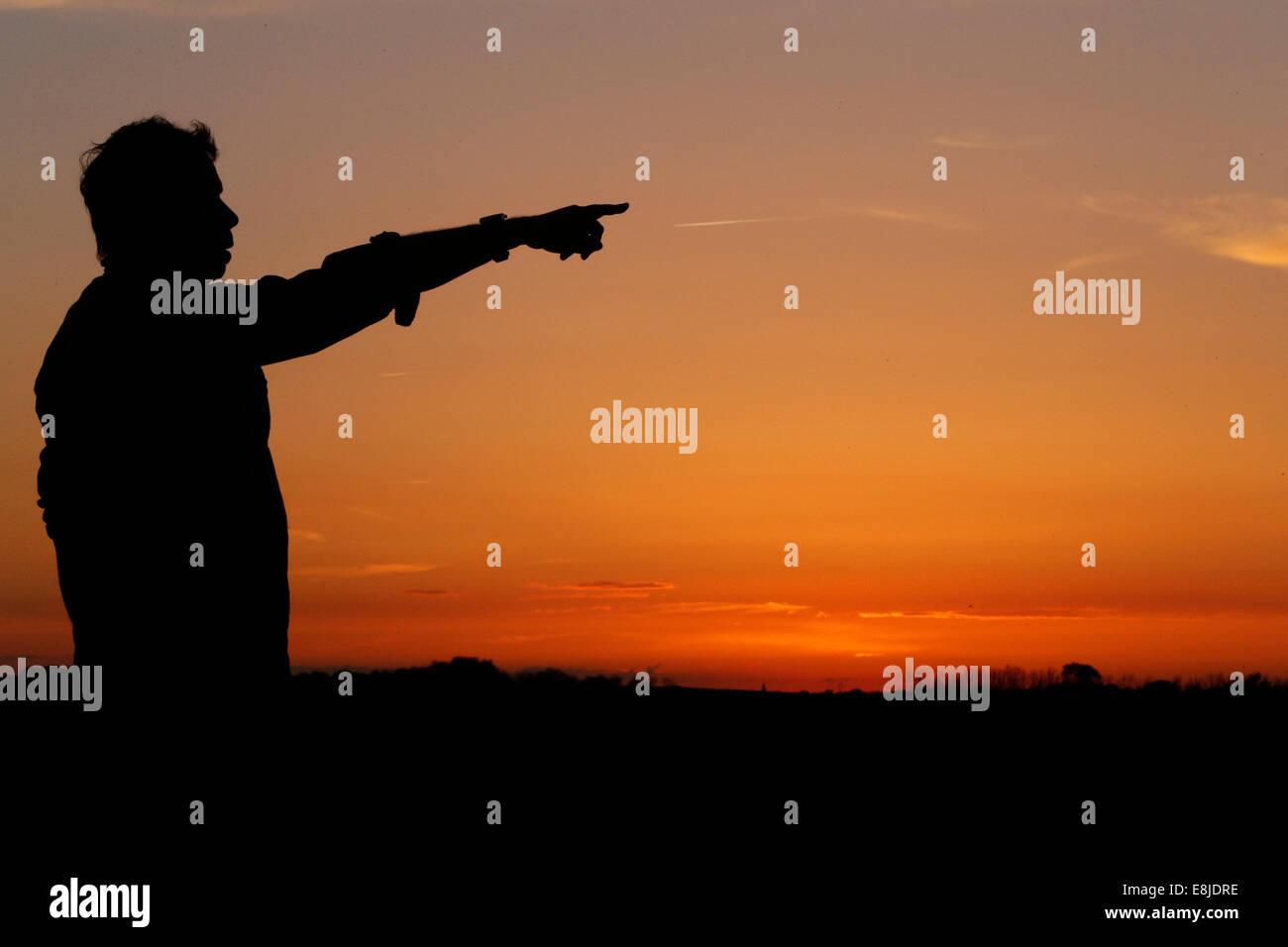 Silhouette d'un homme pointant à l'horizon au coucher du soleil. Photo Stock