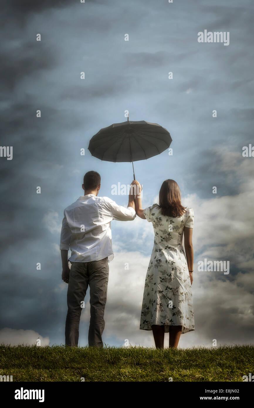 Un couple sur une prairie avec un parapluie Photo Stock