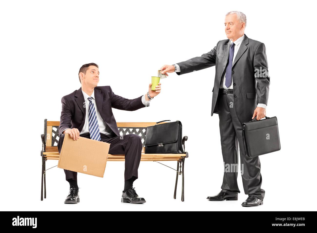 Mature businessman donnant de l'argent à un mendiant isolé sur fond blanc Photo Stock