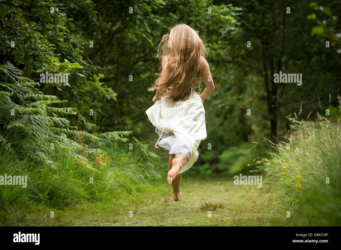 Runaway bride, vue arrière d'un blanc sain jeune femme fille mince avec de longs cheveux blonds s'enfuir pour un chemin woodland forest wearing white robe robe de mariage dans la campagne UK Banque D'Images