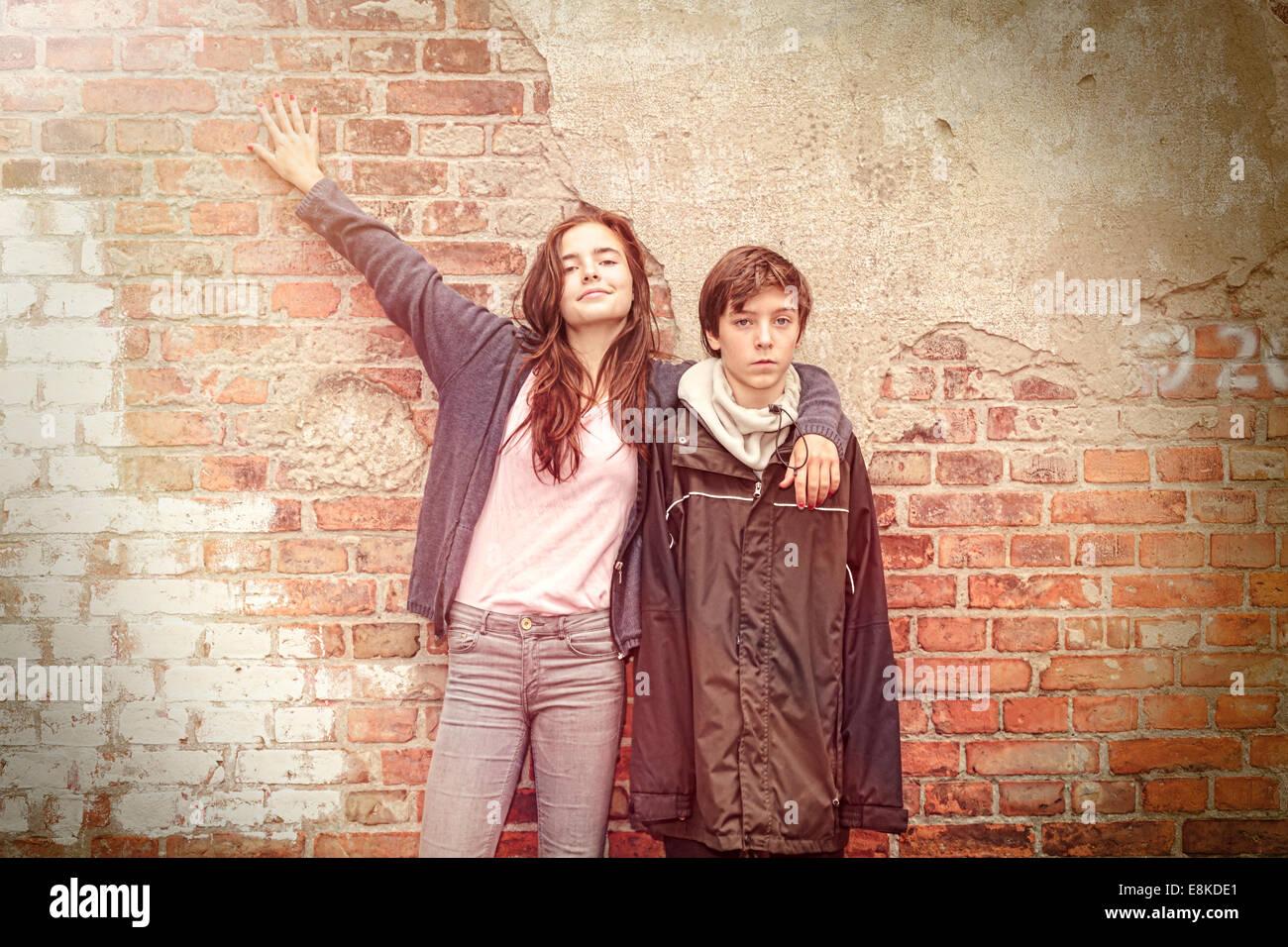Frères et sœurs en face d'un vieux mur de brique grungy Photo Stock