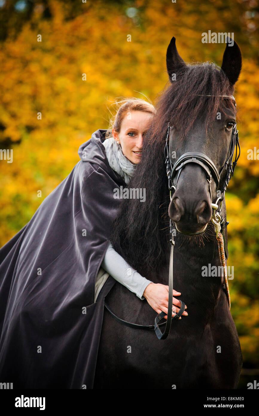 Rider avec le cap sur un Frison, cheval hongre, noir Photo Stock