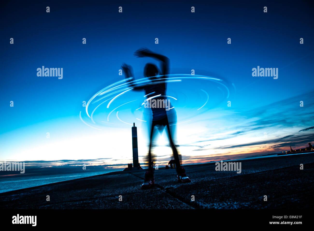 Une femme en silhouette du hula hoop avec un cerceau au crépuscule twilight - longue exposition light trails Photo Stock