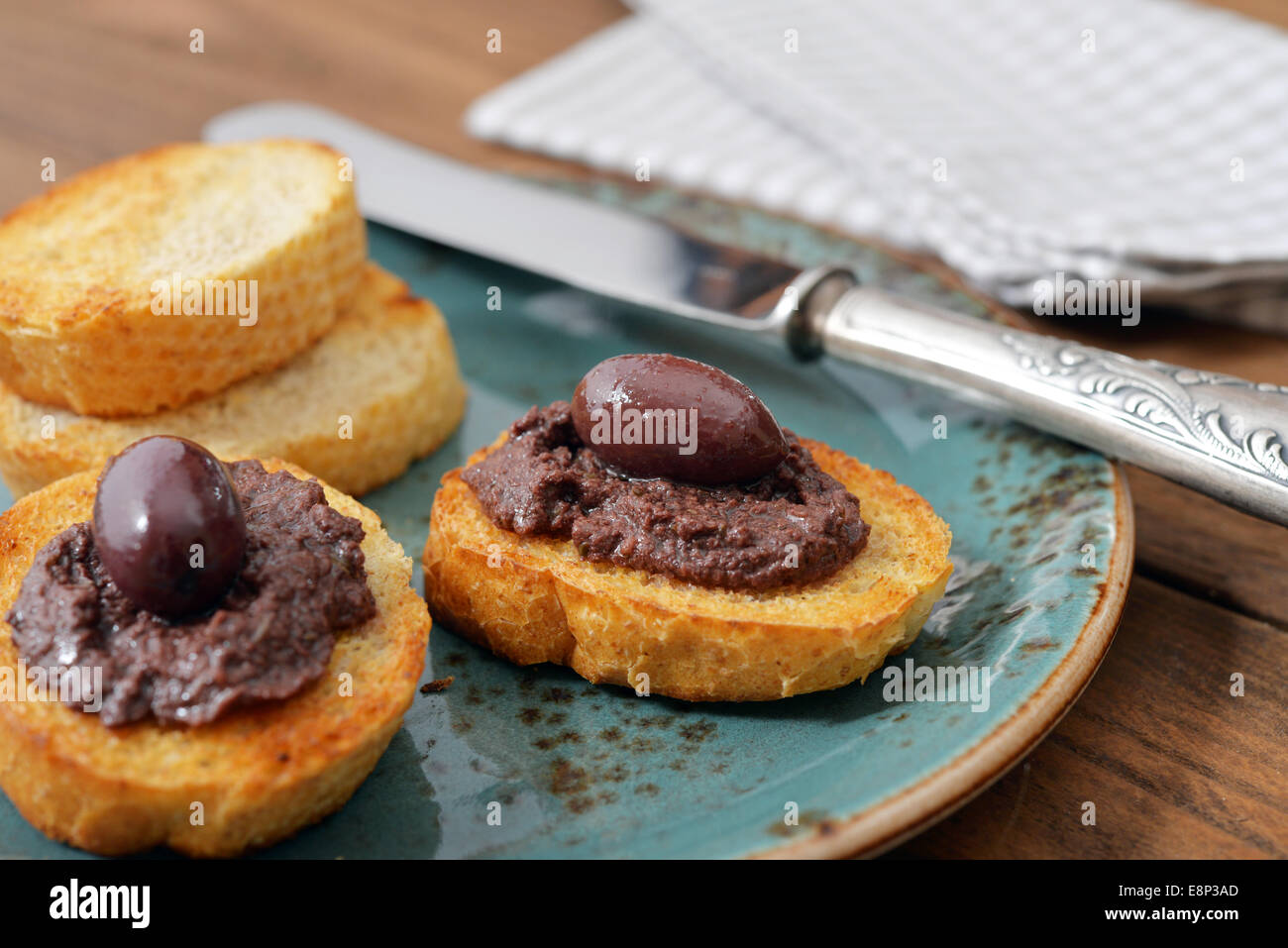 Du pain avec de la pate d'olive sur gros plan de la plaque. La cuisine grecque Photo Stock