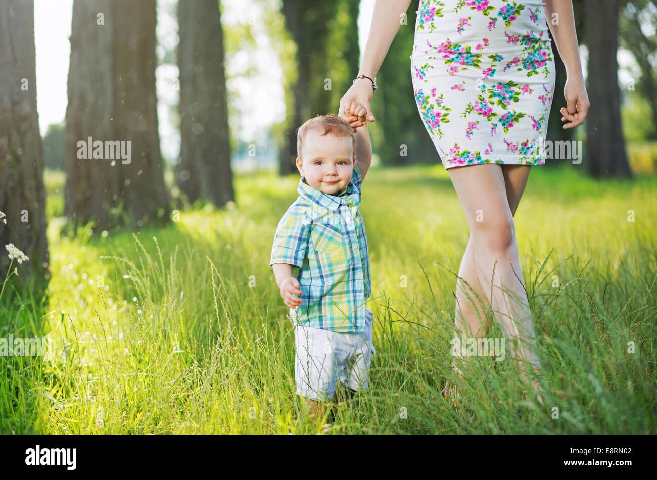 Cheerful enfant tenant la main de maman Photo Stock