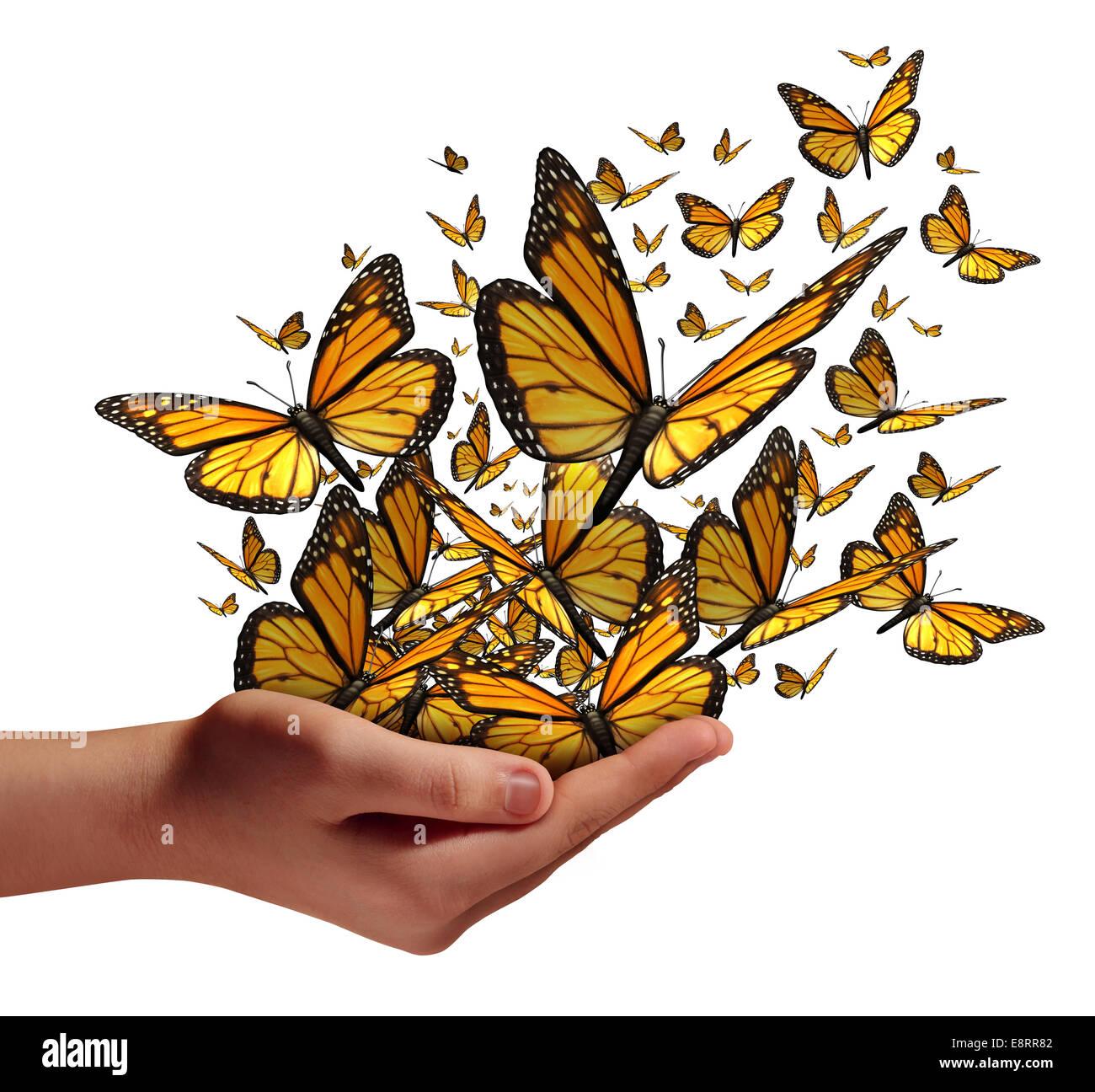 L'espoir et la liberté concept comme une main humaine la libération d'un groupe de papillons comme un symbole pour Banque D'Images