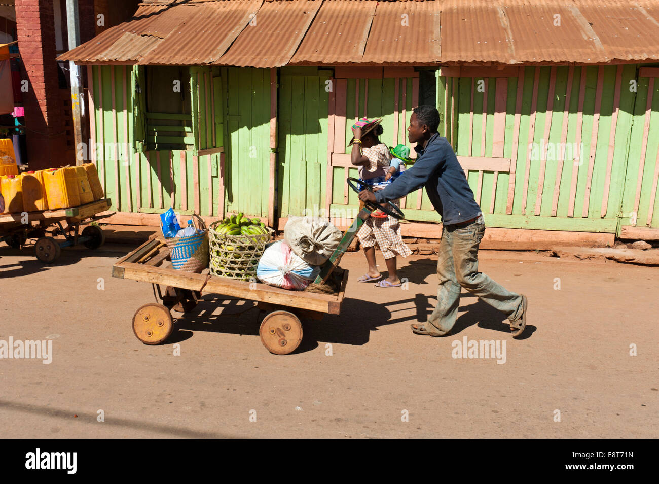 Homme pousse des marchandises sur un panier fait maison, Ambalavao, Madagascar Banque D'Images