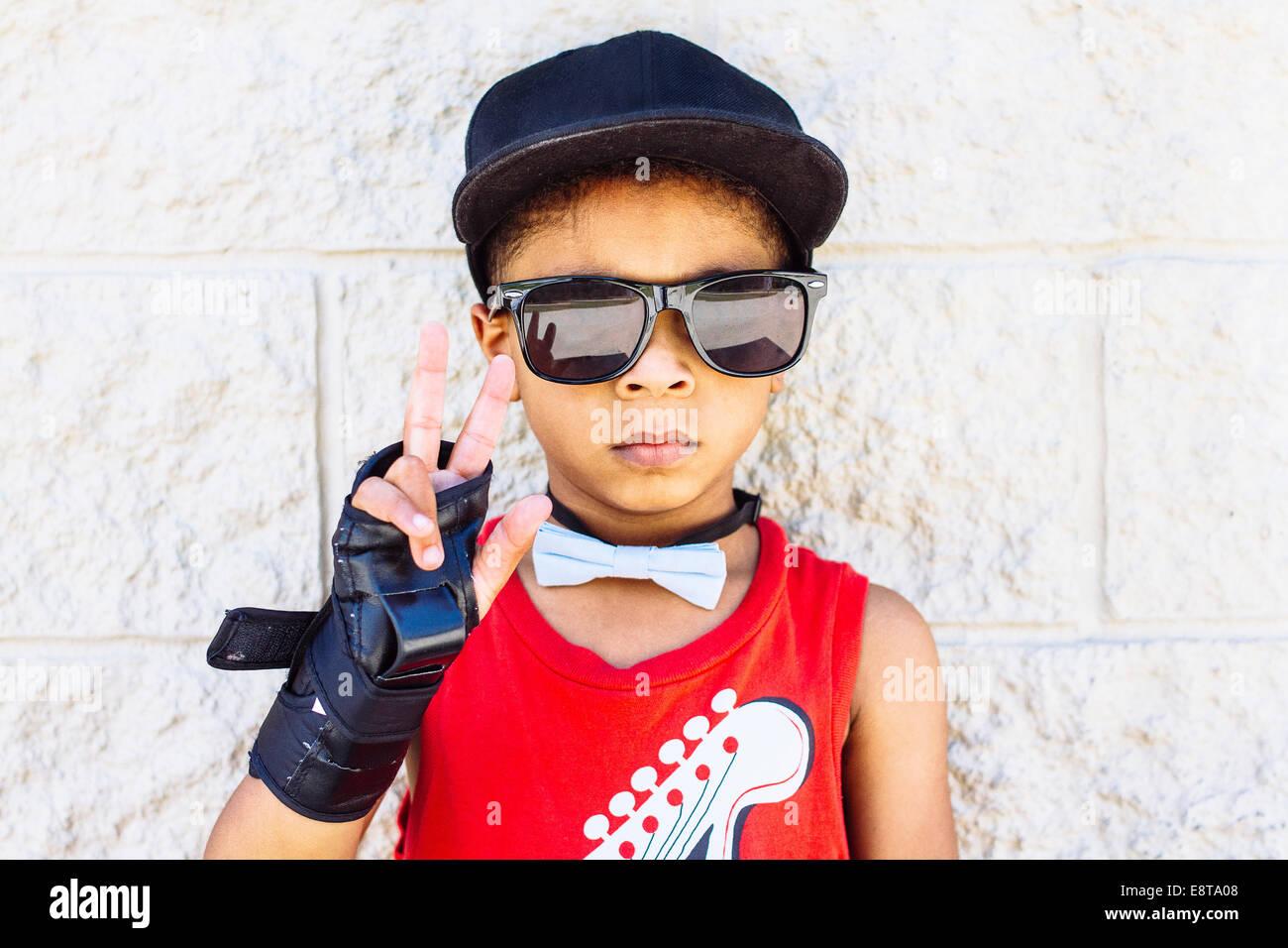 African American boy wearing Bow tie, poignet brace, lunettes de soleil et chapeau de base-ball Banque D'Images