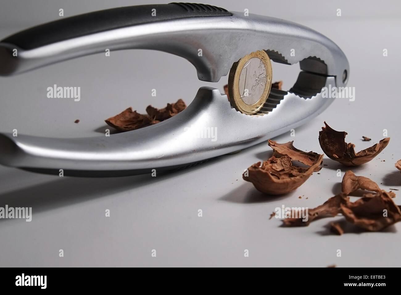 La fissuration d'un écrou avec un casse-noix pour trouver un euro à l'intérieur Photo Stock
