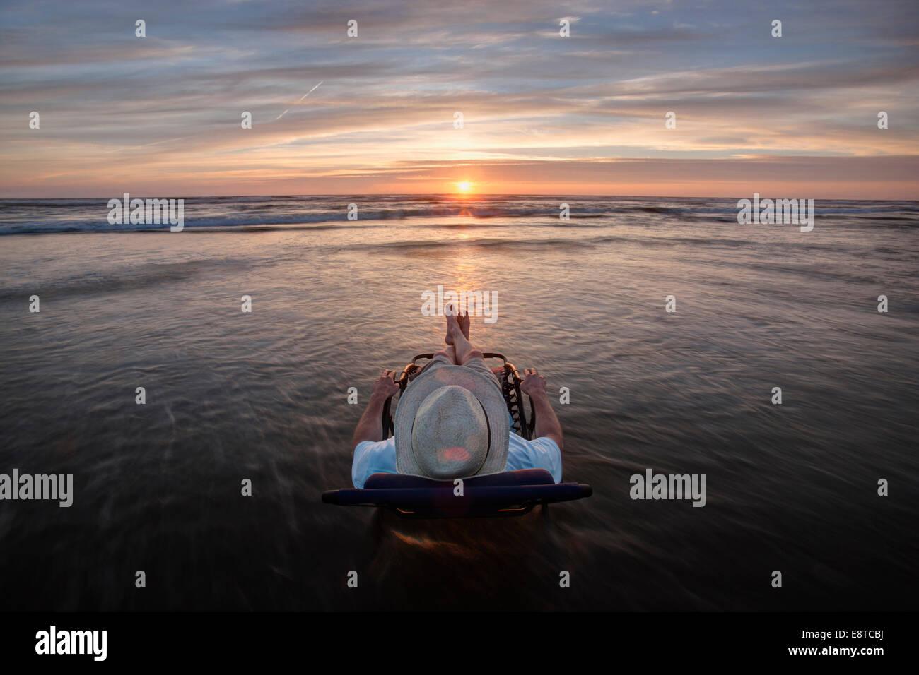 Caucasian man en chaise de terrasse avec vue sur le coucher du soleil sur la plage Photo Stock