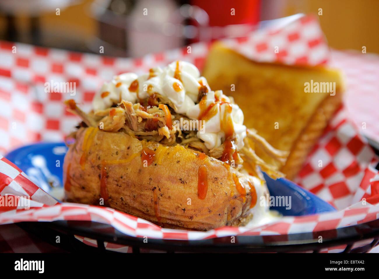 Pomme de terre au four farcies avec un barbecue de porc et surmonté de crème sure et de sauce chaude. Photo Stock