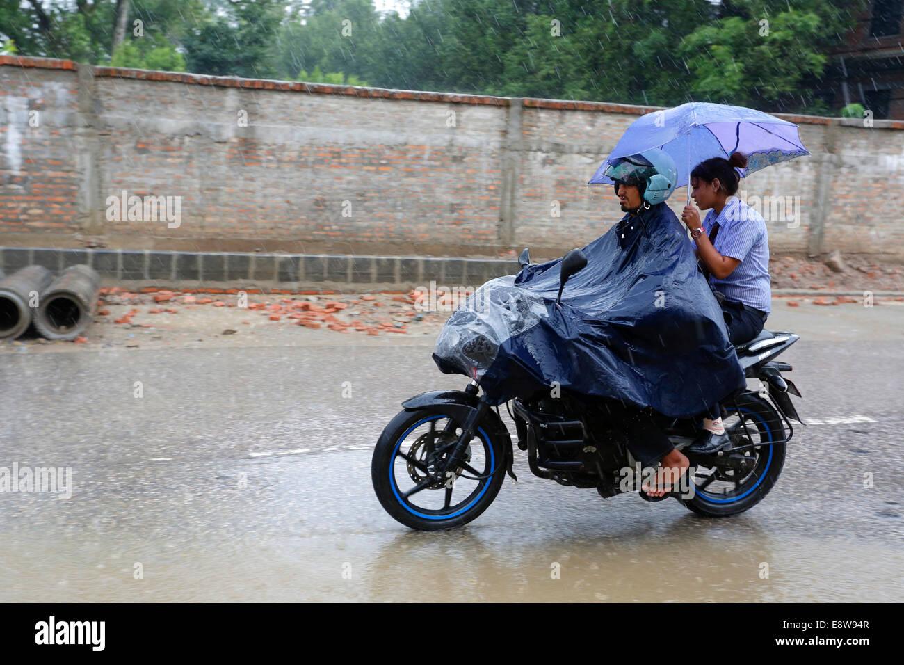 Les gens sur la moto sur route inondée après tempête de mousson, Katmandou, Népal Photo Stock