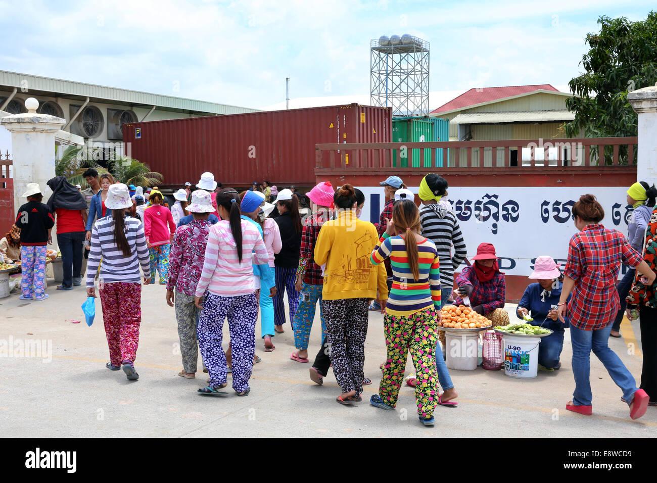 Travailleur féminin entre la porte d'une usine de textile dans la zone industrielle de Pochentong à Photo Stock