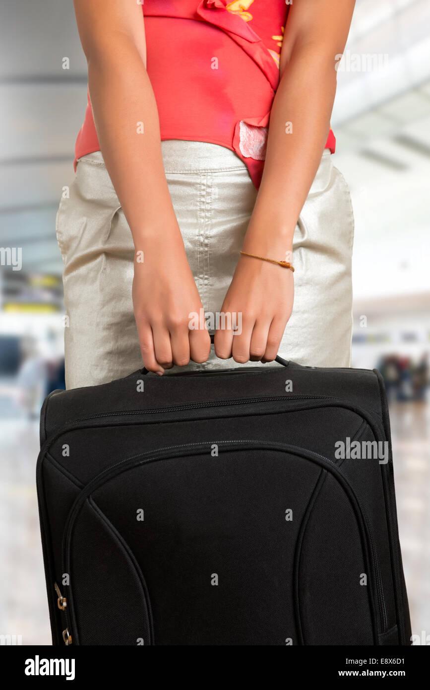 Jeune femme tenant un sac de voyage, dans un aéroport Photo Stock