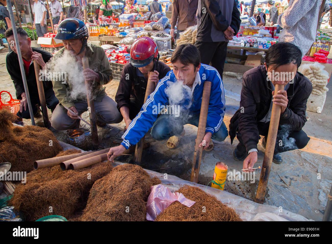 Les hommes Hmong Hill Tribe vietnamiens au marché de Cancau fumer du tabac dans les tuyaux de bambou Banque D'Images