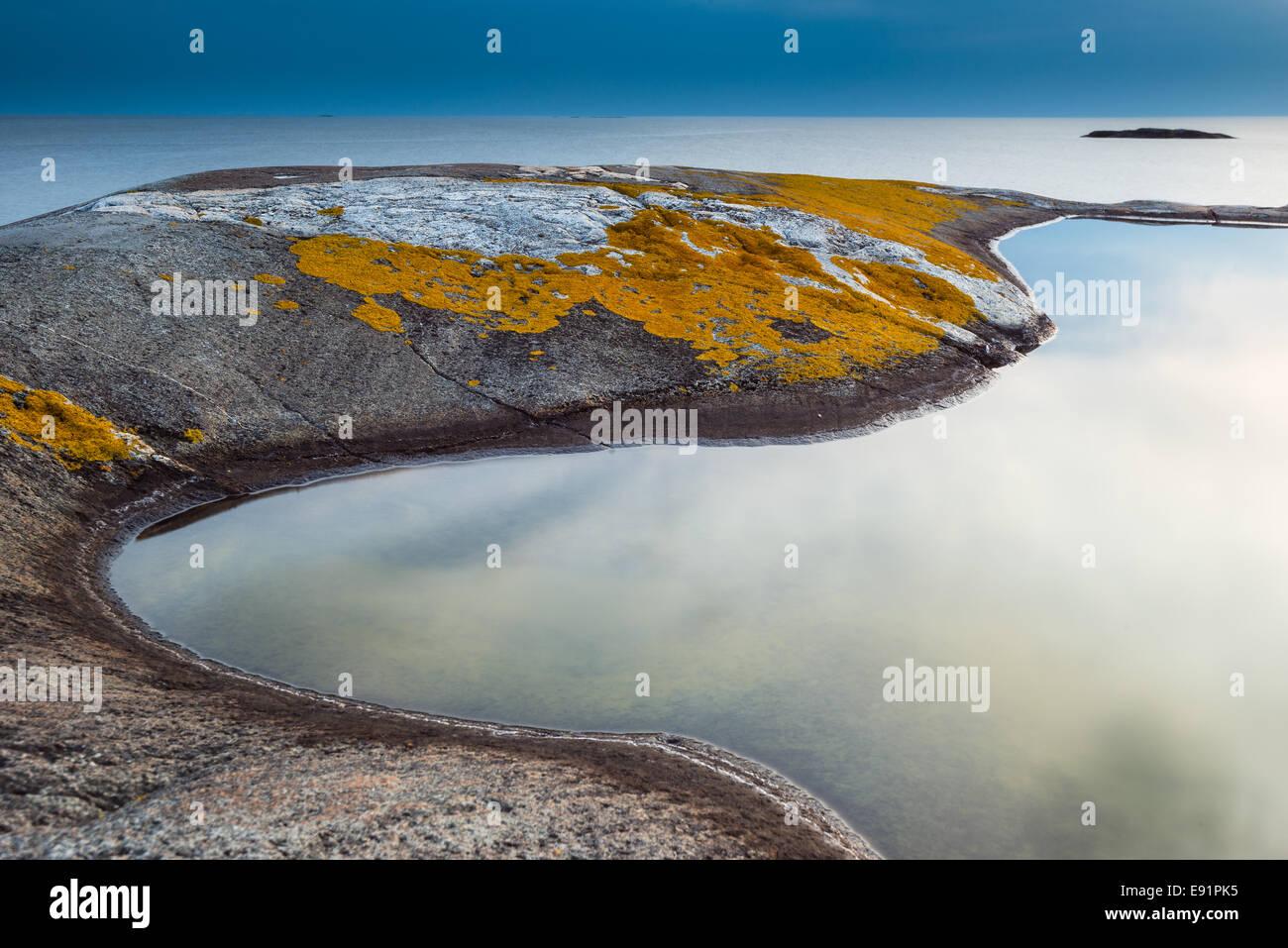Marée lisse extérieure bordée de roches moussues Photo Stock