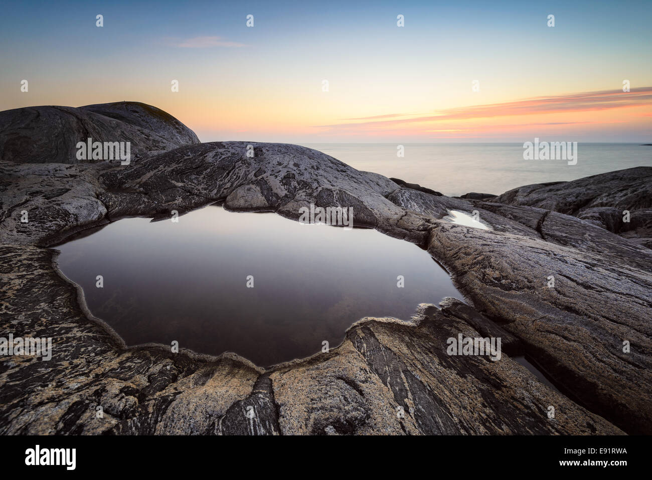 Marée lisse extérieure entourée de rock au coucher du soleil Photo Stock
