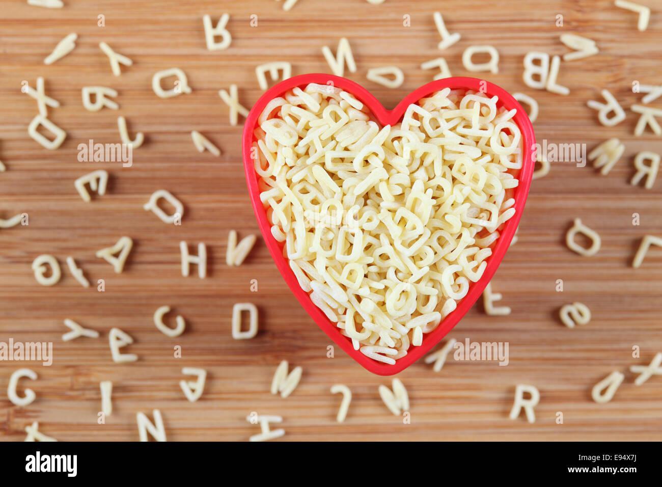 Soupe à l'alphabet de matières premières pâtes dans un bol coeur. Close-up. Photo Stock