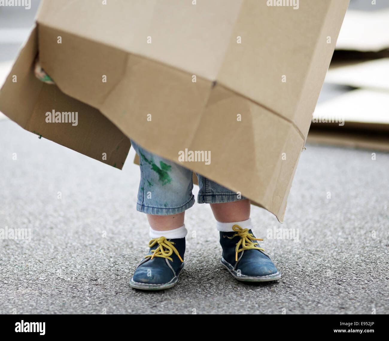 Un enfant jouant avec une boîte en carton. Banque D'Images