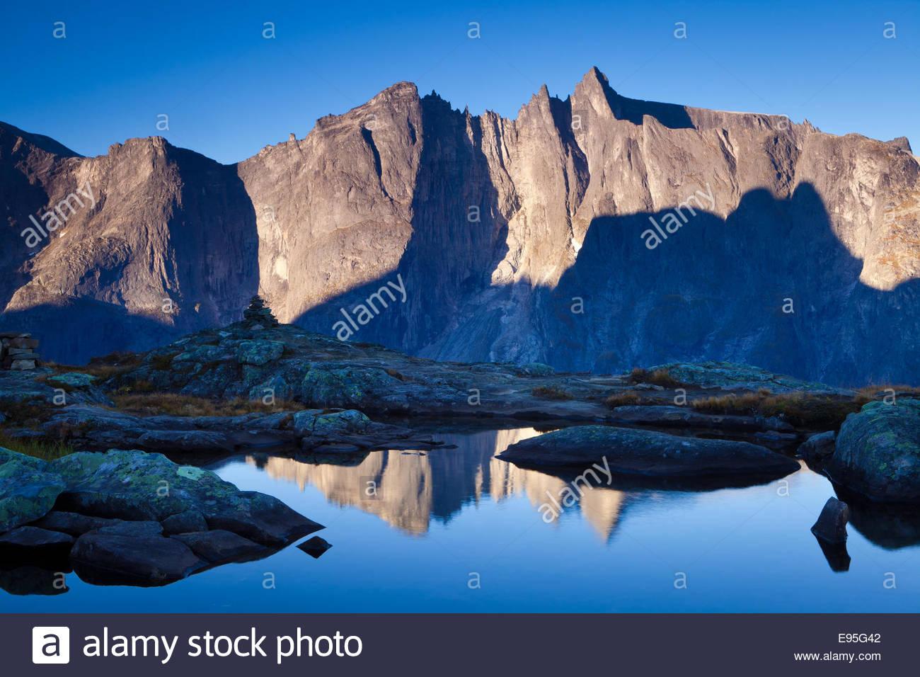 La première lumière sur les sommets et l'Trolltindane 3000 pieds verticalement Troll mur dans la vallée Photo Stock